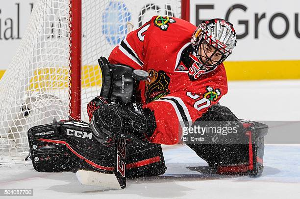 Goalie Corey Crawford of the Chicago Blackhawks swipes at the puck in the third period of the NHL game against the Buffalo Sabres where he made 28...