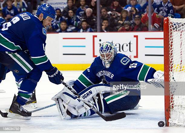 Goalie Cory Schneider and Sami Salo of the Vancouver Canucks watches a Chicago Blackhawks shot hit the post during the third period in NHL action on...