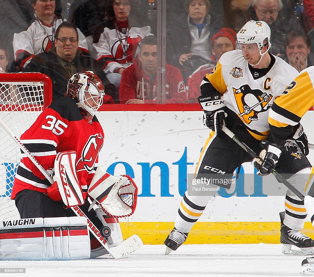 Goalie Cory Schneider #35 of the New Jersey Devils makes a save in front of Sidney Crosby #87 of the Pittsburgh Penguins in the second period of an NHL hockey game at Prudential Center on December 27, 2016 in Newark, New Jersey. Penguins won 5-2.