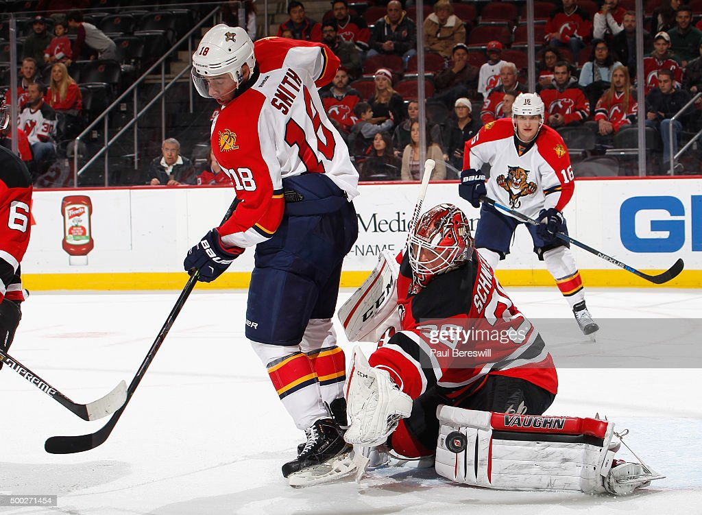 Goalie Cory Schneider #35 of the New Jersey Devils stops a tipped shot by Reilly Smith #18 of the Florida Panthers during the third period of an NHL hockey game at Prudential Center on December 6, 2015 in Newark, New Jersey. Devils on 4-2.