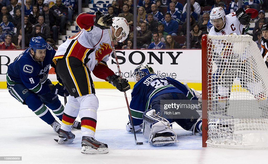 Goalie Cory Schneider #35 of the Vancouver Canucks kicks out his left pad to stop Alex Tanguay #40 of the Calgary Flames in close as Zack Kassian #9 of the Vancouver Canucks and Jarome Iginla #12 of the Calgary Flames looks on during the overtime period of NHL action on January 23, 2013 at Rogers Arena in Vancouver, British Columbia, Canada.