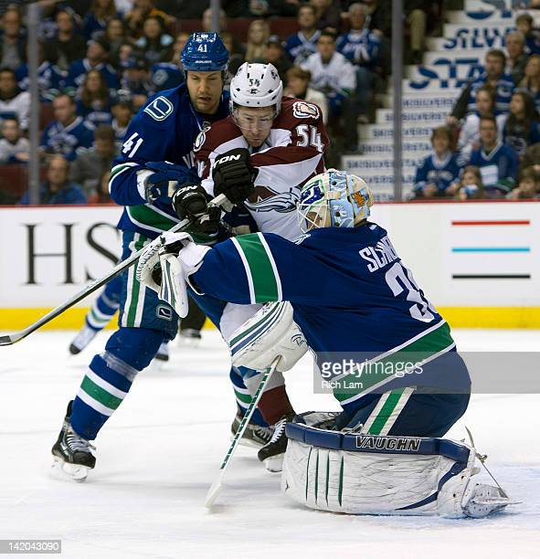 Goalie Cory Schneider of the Vancouver Canucks reaches out to make a glove save while David Jones of the Colorado Avalanche and Andrew Alberts of the...