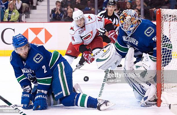 Goalie Cory Schneider of the Vancouver Canucks watches the puck slide past Dan Hamhuis while Sergei Samsonov of the Carolina Hurricanes looks on...