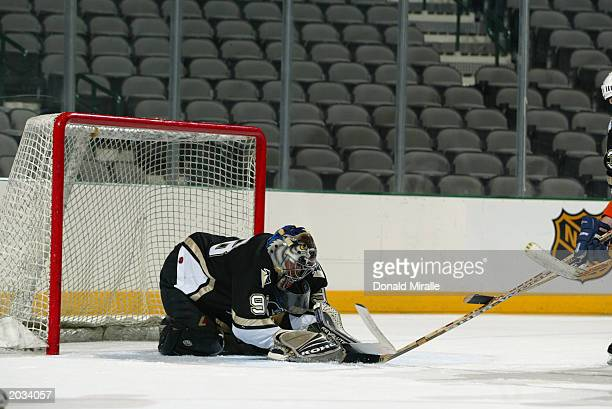 A goalie covers the puck with his glove and blocker during the NHL Concept Shoot on February 22 2003 at the American Airlines Center in Dallas Texas