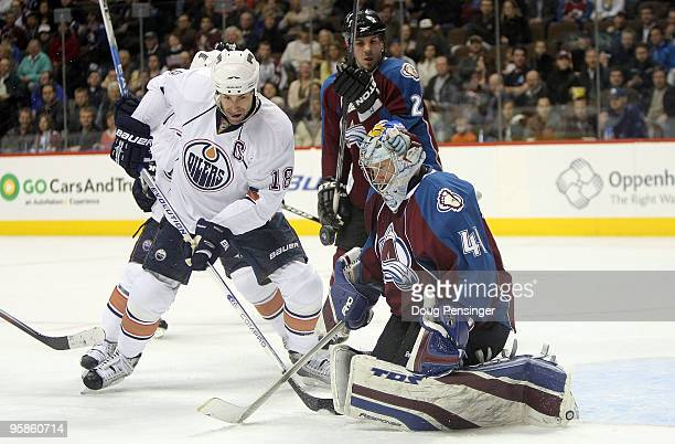 Goalie Craig Anderson of the Colorado Avalanche collects the puck and makes a save as Ethan Moreau of the Edmonton Oilers looks for a rebound during...