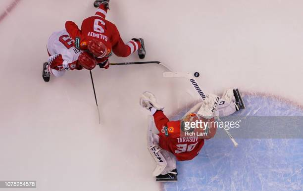Goalie Danil Tarasov of Russia makes a save as Oliver Kjaer of Denmark and Artyom Galimov of Russia battle for position in Group A hockey action of...