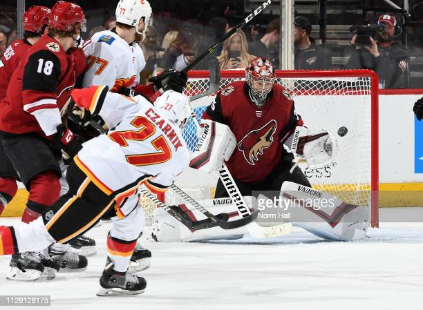 Goalie Darcy Kuemper of the Arizona Coyotes looks to make a glove save on the shot by Austin Czarnik of the Calgary Flames during the second period...
