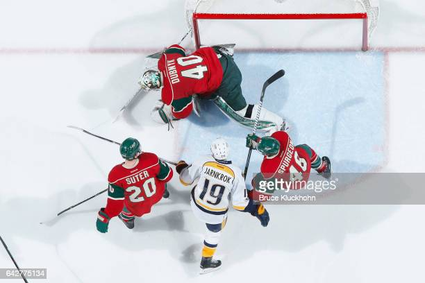 Goalie Devan Dubnyk covers up the puck while his Minnesota Wild teammates Ryan Suter and Jared Spurgeon defend against Calle Jarnkrok of the...
