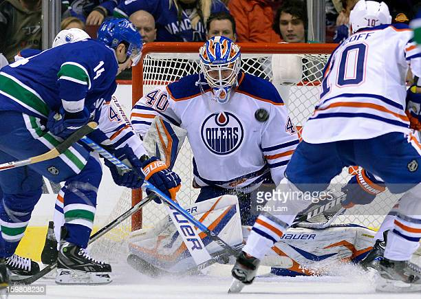 Goalie Devan Dubnyk of the Edmonton Oilers watches an airborne puck fly across the front of the net as Alexandre Burrows of the Vancouver Canucks and...