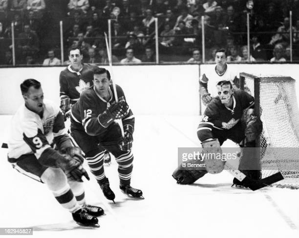 Goalie Don Simmons and Ron Stewart of the Toronto Maple Leafs follow Gordie Howe of the Detroit Red Wings during their game circa 1964 at the Maple...