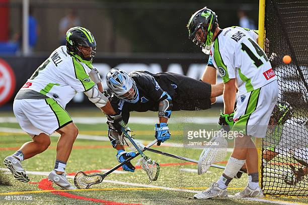 Goalie Drew Adams of the New York Lizards makes a save in the second quarter as Marcus Holman of the Ohio Machine attempts to score while Rob Pannell...
