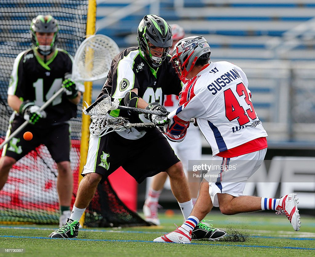 Goalie Drew Adams #14 of the New York Lizzards and teammate Michael Skudin #92 defend a shot by Ari Sussman #43 of the Boston Cannons in the second half of a Major League Lacrosse game at James M. Shuart Stadium on April 28, 2013 in Hempstead, New York.