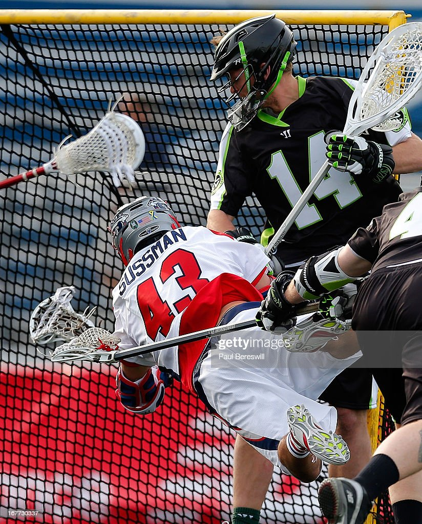 Goalie Drew Adams #14 of the New York Lizzards looks over as Ari Sussman #43 of the Boston Cannons flies through the air as he shoots the ball for a goal in the second half of a Major League Lacrosse game at James M. Shuart Stadium on April 28, 2013 in Hempstead, New York.