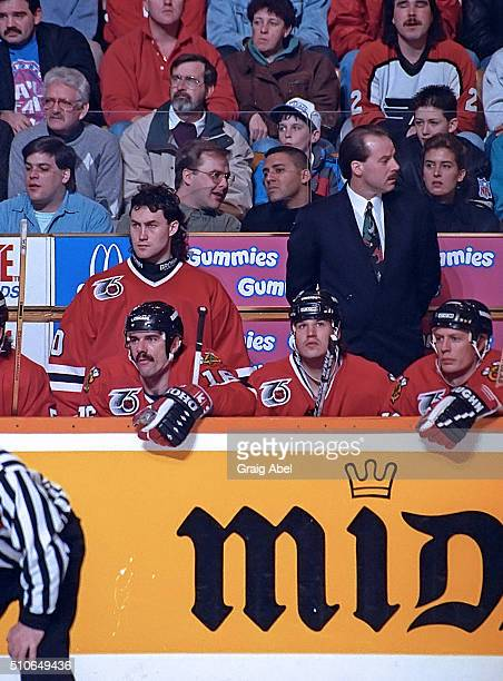 Goalie Ed Belfour and head coach Mike Keenan of the Chicago Black Hawks watch the play develop from behind the bench against the Toronto Maple Leafs...