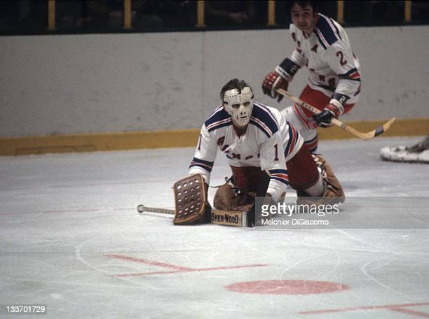 Goalie Ed Giacomin of the New York Rangers covers the puck as teammate Brad Park skates behind him during their game circa 1973 at the Madison Square...