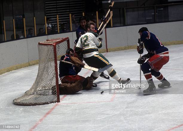 Goalie Ed Giacomin of the New York Rangers is crashed into by Tommy Williams of the Minnesota North Stars as Ron Stewart and Jim Neilson of the...