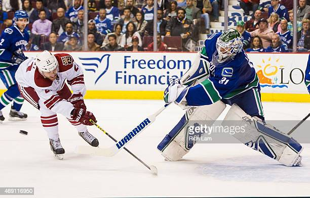 Goalie Eddie Lack of the Vancouver Canucks clears the puck while pressured by Jordan Szwarz of the Arizona Coyotes in NHL action on April 2015 at...