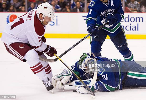 Goalie Eddie Lack of the Vancouver Canucks dives to cover up the puck before Jordan Szwarz of the Arizona Coyotes can get his stick on it in NHL...
