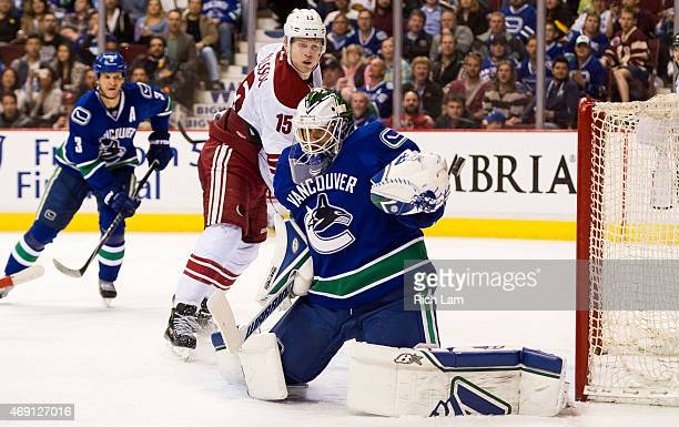Goalie Eddie Lack of the Vancouver Canucks makes a glove save while Henrik Samuelsson of the Arizona Coyotes looks on in NHL action on April 9 2015...