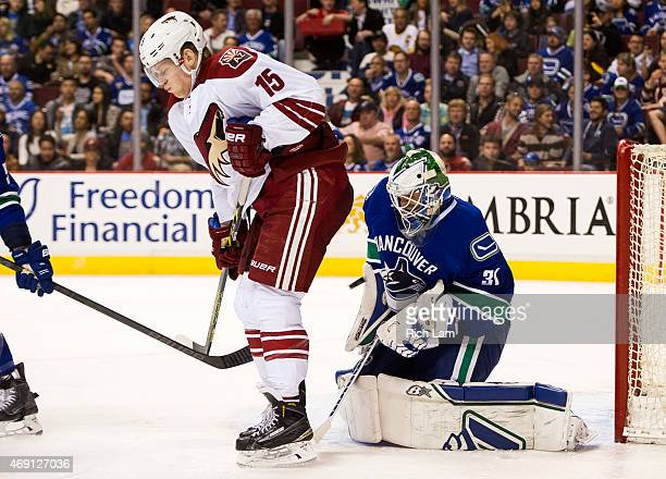 Goalie Eddie Lack of the Vancouver Canucks makes a save while screened by Henrik Samuelsson of the Arizona Coyotes in NHL action on April 9 2015 at...