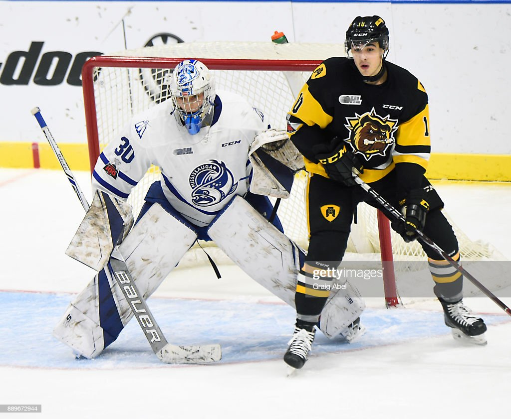 Goalie Emanuel Vella #30 of the Mississauga Steelheads and Nicholas Caamano #10 of the Hamilton Bulldogs prepare for a shot during game action on December 10, 2017 at Hershey Centre in Mississauga, Ontario, Canada.