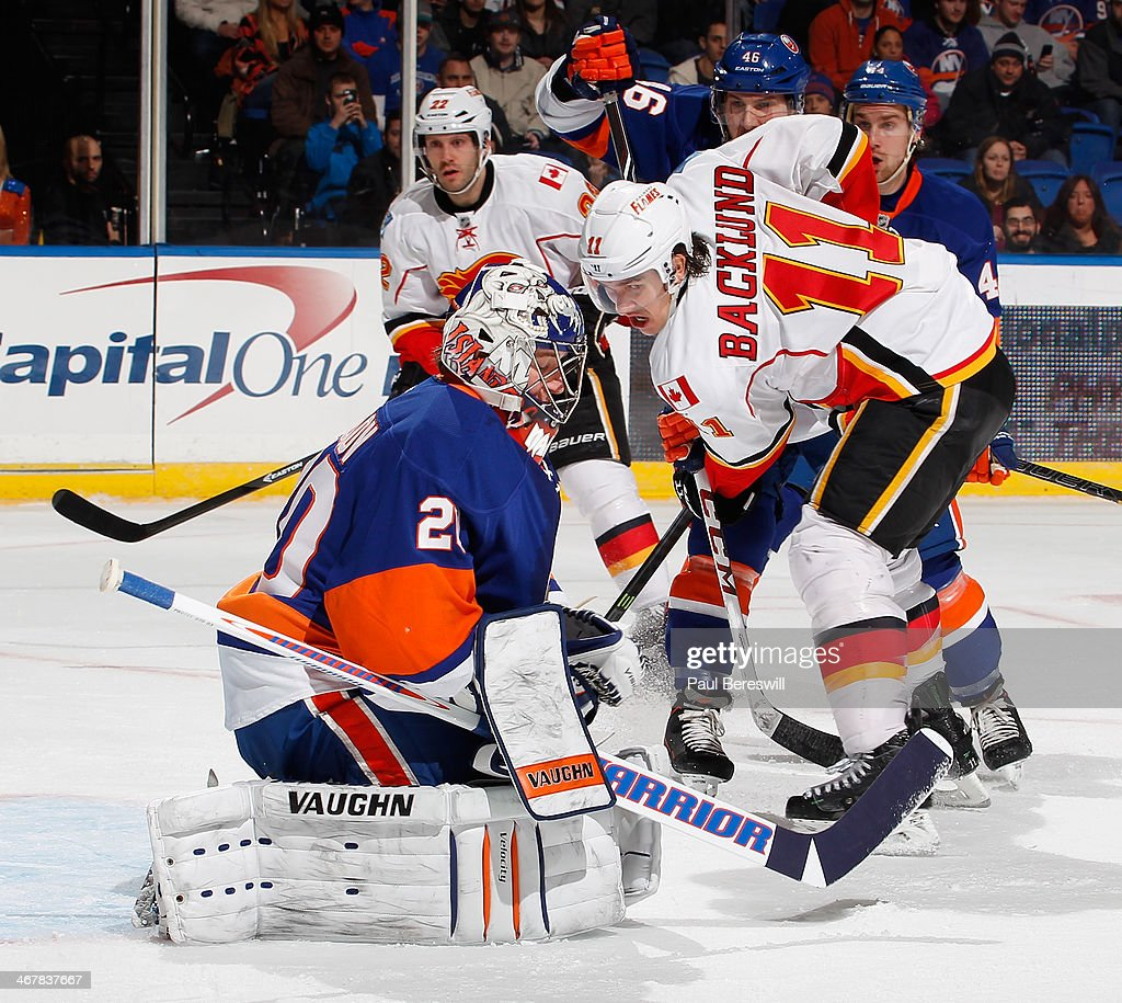Goalie Evgeni Nabokov #20 of the New York Islanders stops a shot by Mikael Backlund #11 of the Calgary Flames during an NHL hockey game at Nassau Veterans Memorial Coliseum on February 6, 2014 in Uniondale, New York.
