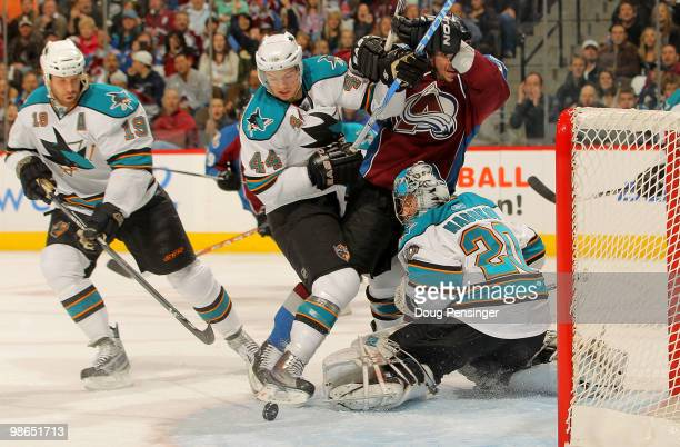 Goalie Evgeni Nabokov of the San Jose Sharks eyes the puck as Ryan Wilson of the Sharks defends against Scott Hannan of the Colorado Avalanche during...