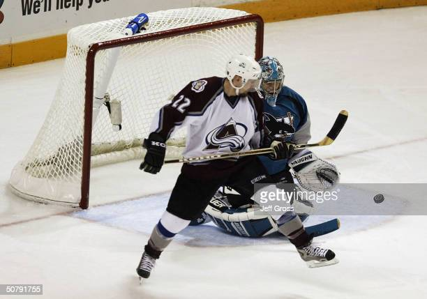 Goalie Evgeni Nabokov of the San Jose Sharks makes a save on Steve Konowalchuk of the Colorado Avalanche during the second period of game five of the...