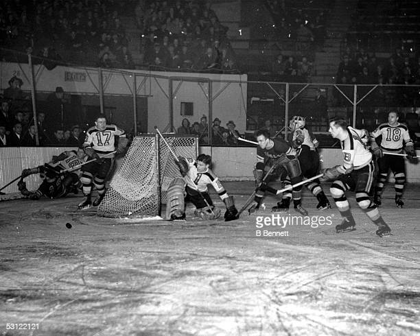 Goalie Frank Brimsek of the Boston Bruins looks on as teammate Bobby Bauer looks to skate up the ice with the puck during an NHL game against the New...