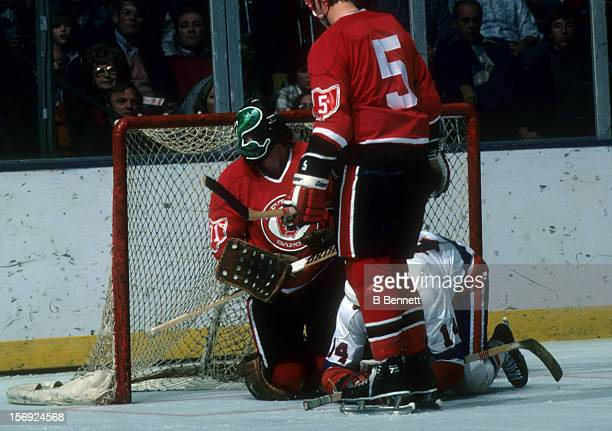 Goalie Gary 'Cobra' Simmons of the Cleveland Barons is run into by Bob Bourne of the New York Islanders as Greg Smith of the Barons looks on during...
