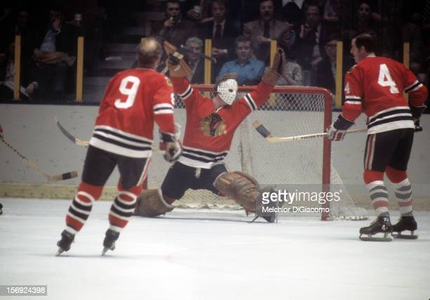 Goalie Gary Smith of the Chicago Blackhawks makes the save as teammates Doug Jarrett and Bobby Hull look on during an NHL game against the New York...