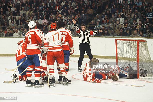 Goalie Gerry Cheevers catches the puck as he falls on top of teammate Paul Shmyr of team Canada during a game against the Soviet Union during a...
