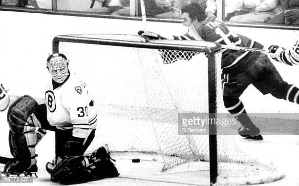 Goalie Gerry Cheevers of the Boston Bruins can't save the goal as Mario Tremblay of the Montreal Canadiens skates around the net after scoring during...