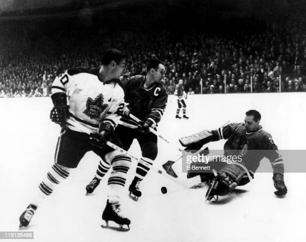 Goalie Glen Hall of the Chicago Blackhawks looks to make the save as his teammate Pierre Pilote blocks out Bob Pulford of the Toronto Maple Leafs...