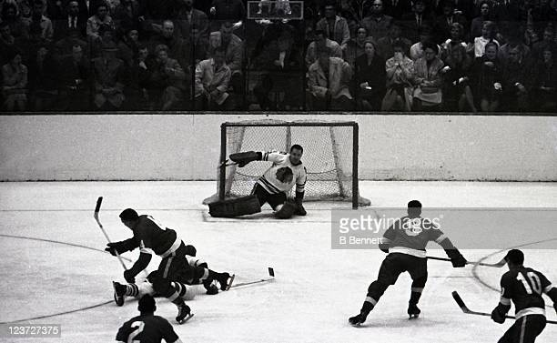 Goalie Glen Hall of the Chicago Blackhawks makes the save as Gordie Howe Bill Gadsby and Alex Delvecchio of the Detroit Red Wings look for a rebound...