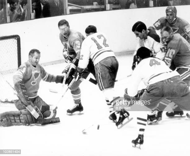 Goalie Glenn Hall and teammate Al Arbour of the St Louis Blues defend the net as Yvan Cournoyer and Jean Beliveau of the Montreal Canadiens look to...