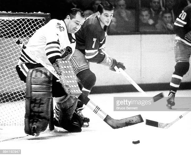 Goalie Glenn Hall of the Chicago Blackhawks clears the puck as Rod Gilbert of the New York Rangers skates around the net on November 17 1965 at the...