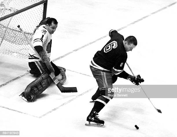 Goalie Glenn Hall of the Chicago Blackhawks defends the net as Pat Hannigan of the New York Rangers goes for a backhand shot circa 1961 at the...