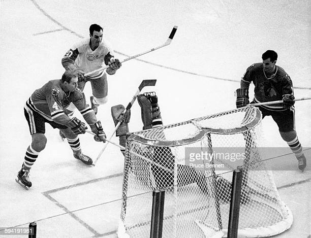 Goalie Glenn Hall of the Chicago Blackhawks falls backwards after making the save on Dean Prentice of the Detroit Red Wings as Elmer Vasko # and Al...
