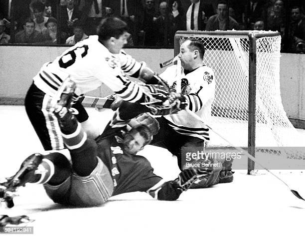 Goalie Glenn Hall of the Chicago Blackhawks is nailed in the face by the stick of Orland Kurtenbach of the New York Rangers as Chico Maki of the...
