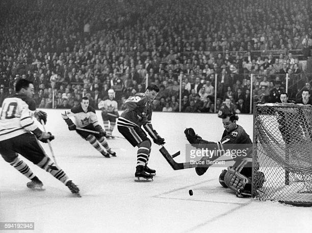 Goalie Glenn Hall of the Chicago Blackhawks looks to make the save on George Armstrong of the Toronto Maple Leafs as Al MacNeil of the Blackhawk...