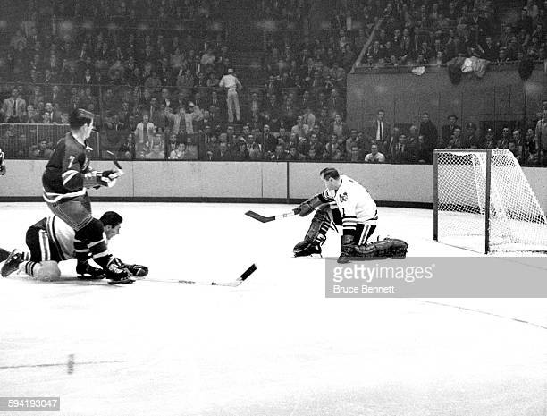 Goalie Glenn Hall of the Chicago Blackhawks looks to make the save on Rod Gilbert of the New York Rangers on November 17 1965 at the Madison Square...