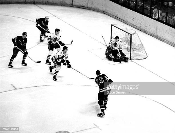 Goalie Glenn Hall of the Chicago Blackhawks makes the save on Don Marshall of the New York Rangers as Wayne Hillman Al MacNeil of the Blackhawks and...