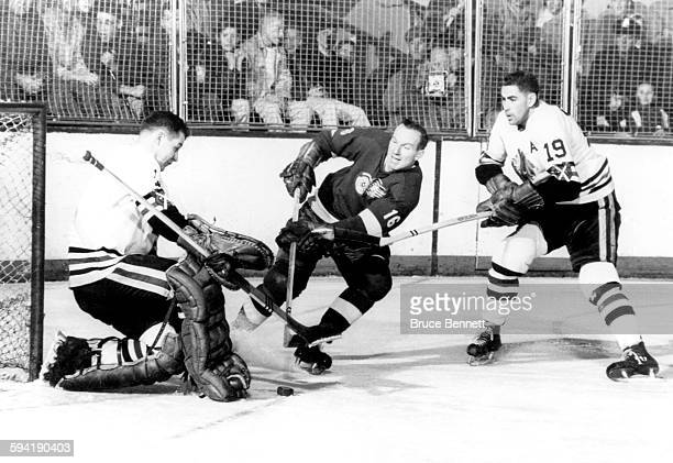 Goalie Glenn Hall of the Chicago Blackhawks makes the save on Jack McIntyre of the Detroit Red Wings as Hall's teammate Dollard St. Laurent helps...