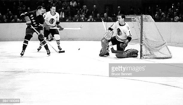 Goalie Glenn Hall of the Chicago Blackhawks makes the save on the shot by Earl Ingarfield of the New York Rangers as Pierre Pilote of the Blackhawks...