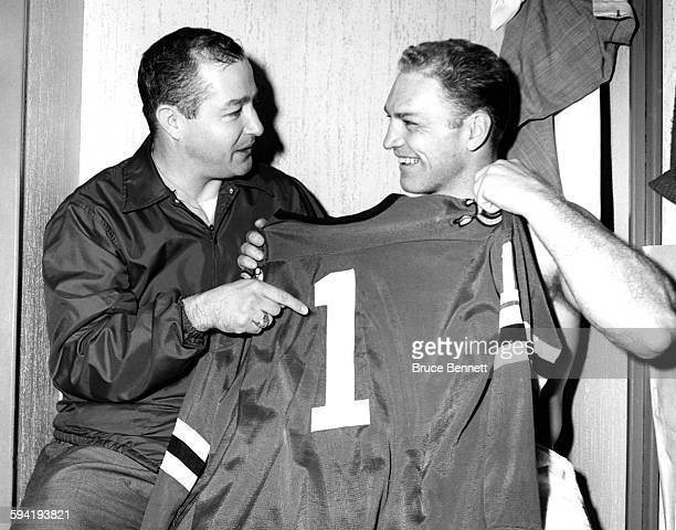 Goalie Glenn Hall of the Chicago Blackhawks shows teammate Bobby Hull the number 1 as Hull will go for his 51st goal of the season against the...