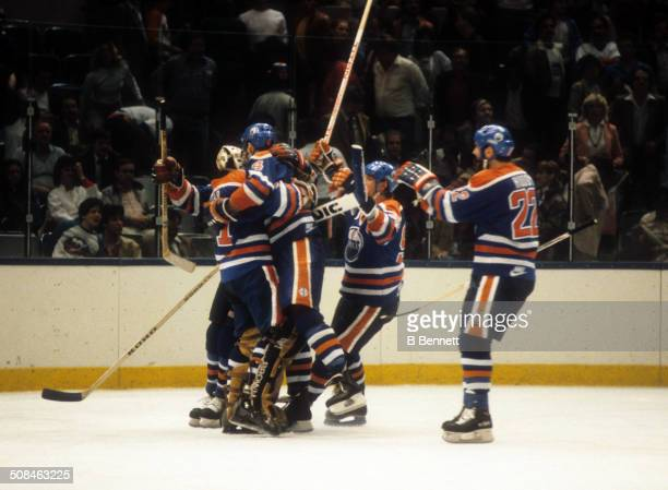 Goalie Grant Fuhr Kevin Lowe Wayne Gretzky and Charlie Huddy of the Edmonton Oilers celebrate on the ice after defeating the New York Islanders in...