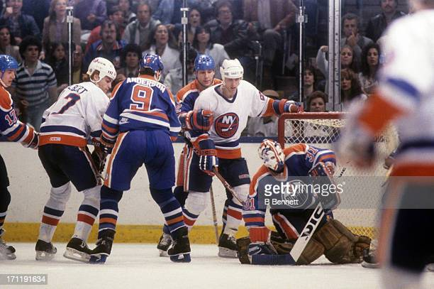 Goalie Grant Fuhr of the Edmonton Oilers covers up the puck as Mike Bossy of the New York Islanders looks for a rebound during the 1984 Stanley Cup...