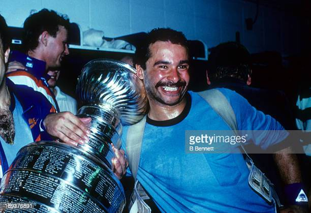 Goalie Grant Fuhr of the Edmonton Oilers poses with the Stanley Cup Trophy in the locker room after the Oilers was victorious in the 1985 Stanley Cup...