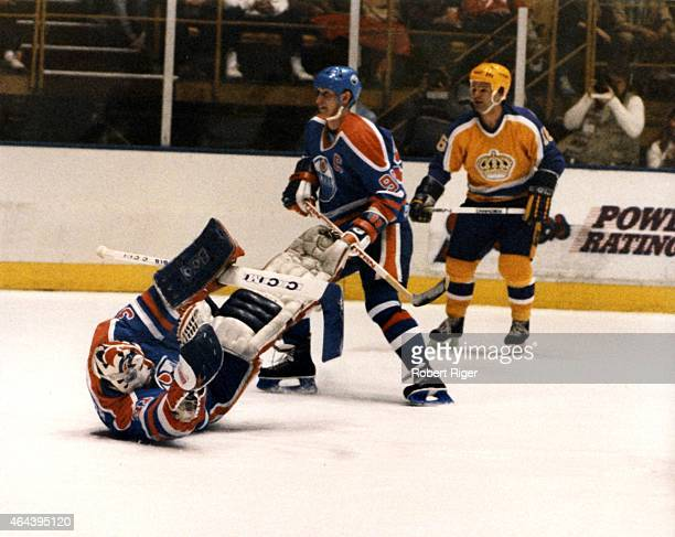 Goalie Grant Fuhr of the Edmonton Oilers tries to make the save as his teammate Wayne Gretzky skates by with Marcel Dionne of the Los Angeles Kings...